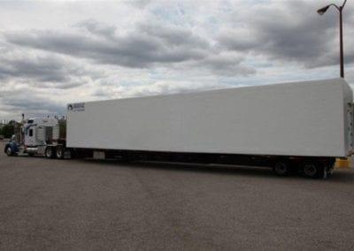 A large truck moving a polar leasing white freezer box rental