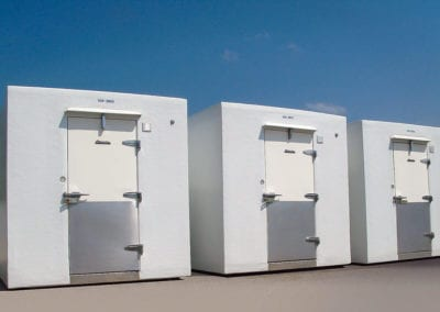 Three large white temporary freezers outside on concrete