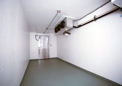 Inside view of a Polar Leasing reefer container rental with white walls and grey flooring