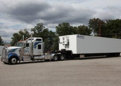 A white and blue semi truck pulling a white polar leasing cooler box rental